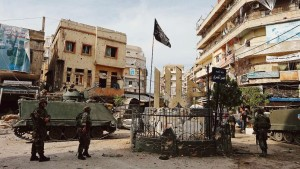 Lebanese army soldiers stand near damaged buildings after being deployed to tighten security, in Tripoli