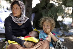 A displaced family from the minority Yazidi sect, fleeing the violence in the Iraqi town of Sinjar, waits for food while resting at the Iraqi-Syrian border crossing in Fishkhabour, Dohuk province August 13, 2014. REUTERS/Youssef Boudlal (IRAQ - Tags: CIVIL UNREST POLITICS) - RTR42BTM